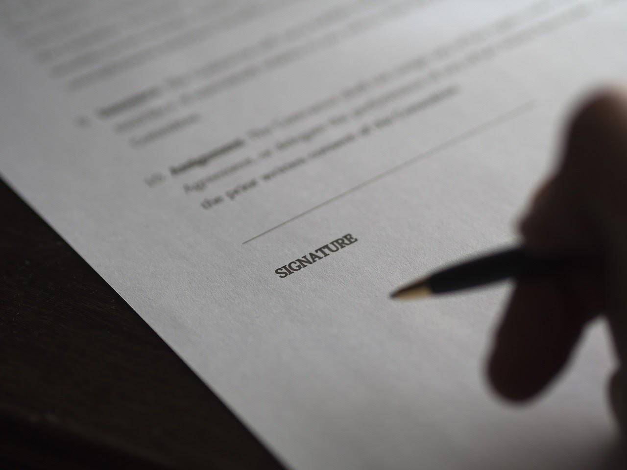 A person is signing a legal document, a process involved in understanding insurance benefits.