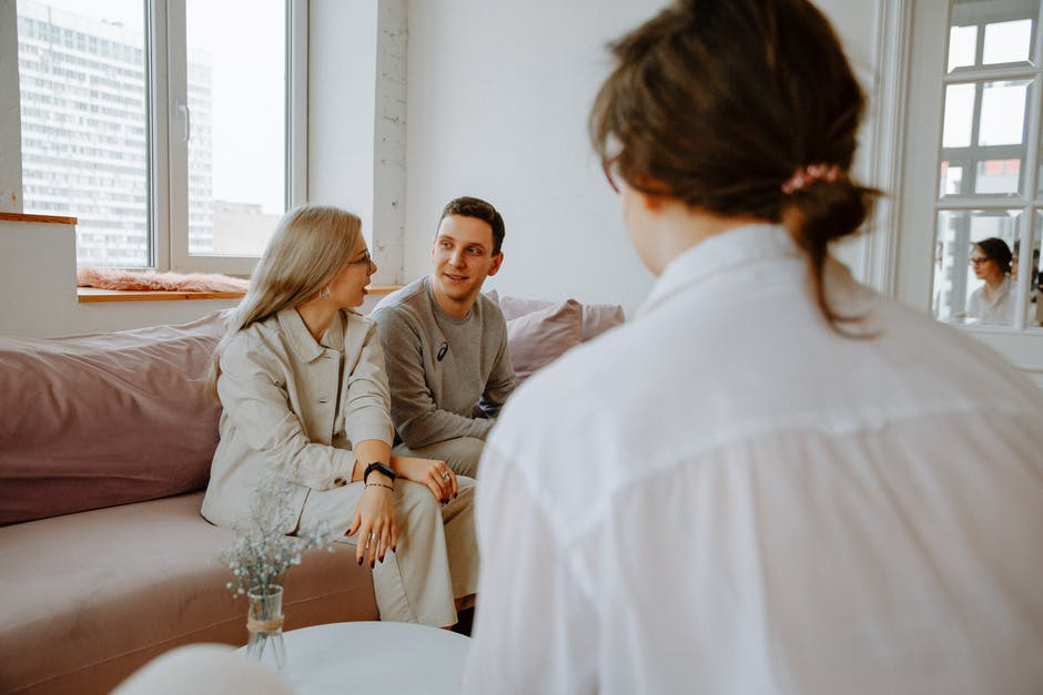 A woman talking to a couple on a couch
