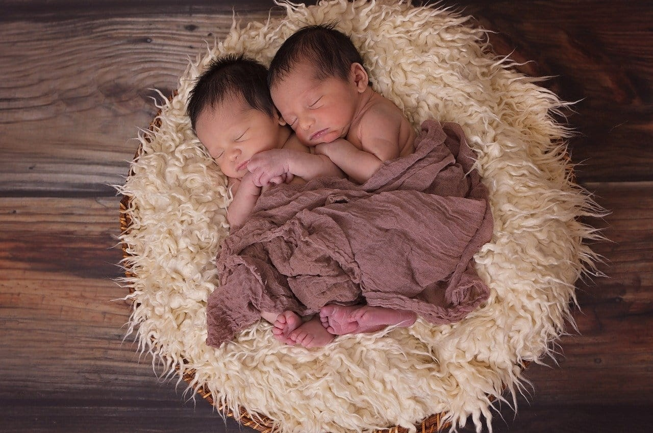 Two newborn babies sleep are lying next to one another.  A woman may have two children in total during her reproductive years, and this is her total fertility rate.