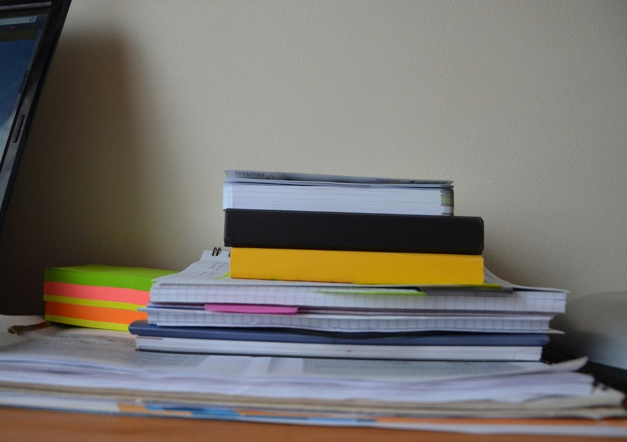 Here we see a stack of books and notebooks associated with education. Education level plays a role in total fertility rates across generations of women.