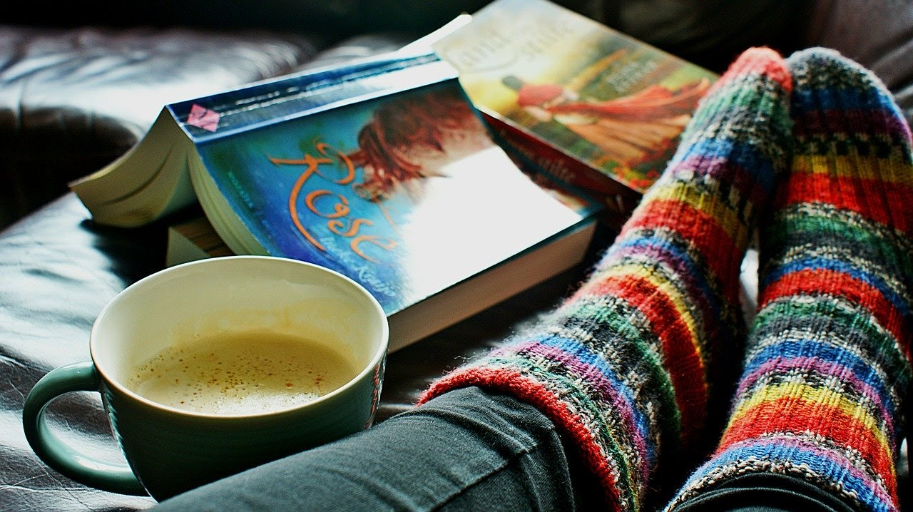 A woman cozy in bed with a mug of tea and a couple of books, relaxing during her IVF journey.