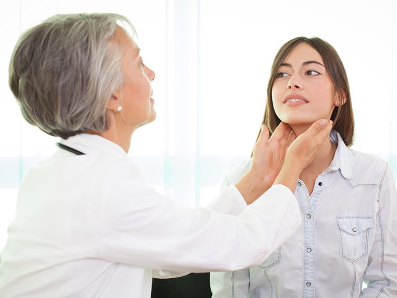 A female doctor checks a woman's thyroid .