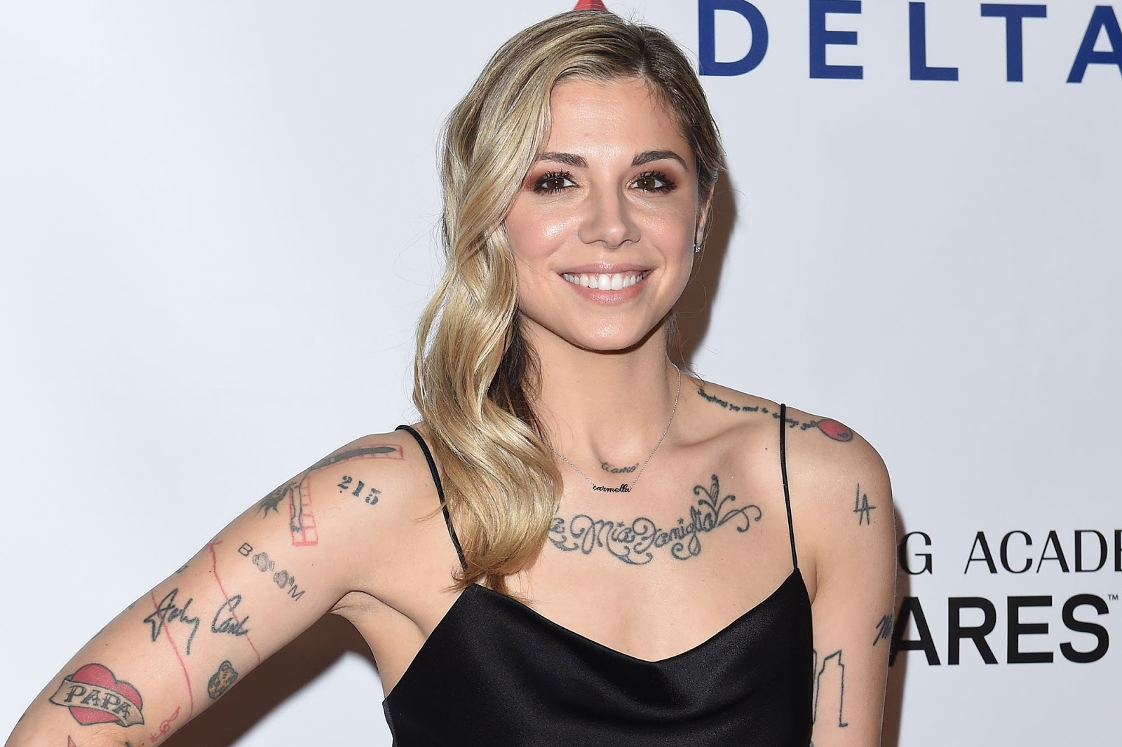 Christina Perri smiles at a red carpet event, proudly displaying her tattoos.