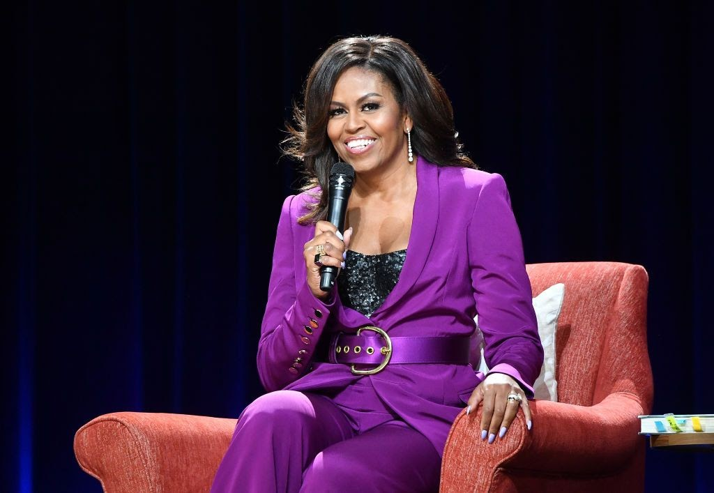Michelle Obama poses while sitting on stage for her book Becoming, in which she details her own experience with miscarriage and IVF.