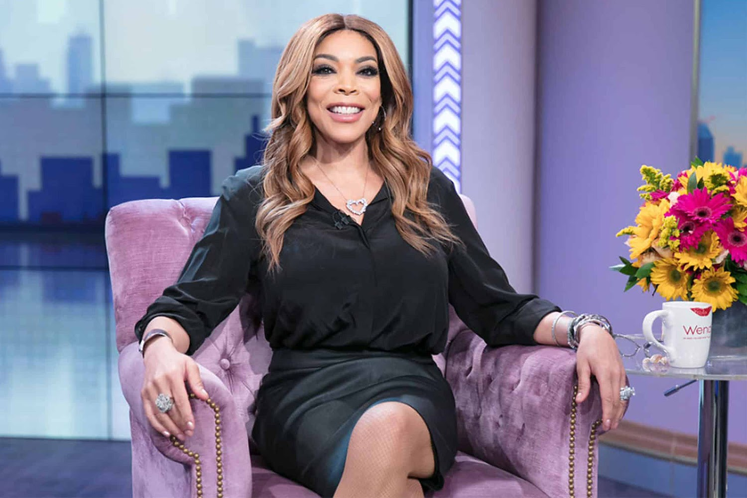 Wendy Williams poses in her iconic purple chair on the set of the Wendy Williams show.