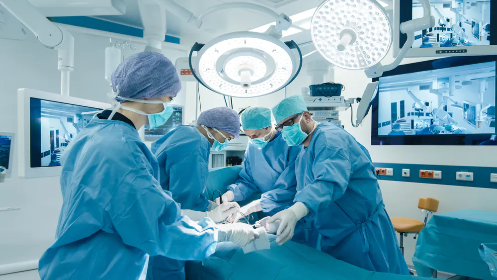 Photo of surgeons in the middle of surgery wearing blue gowns