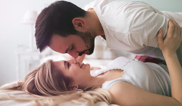 a man on top of a woman on a bed in an intimate embrace