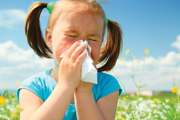 Photo of girl in blue shirt sneezing into a white tissue while outdoors in a meadow