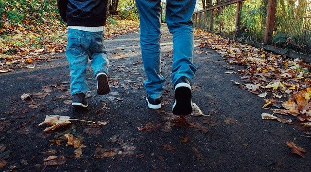 A dad and his son go for a walk in the fall