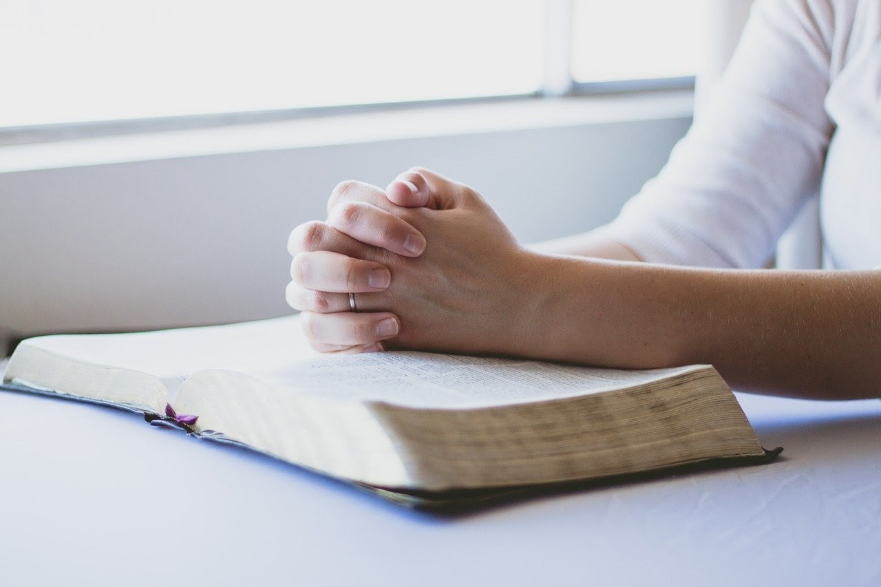 A Christian places their hands on the bible in prayer