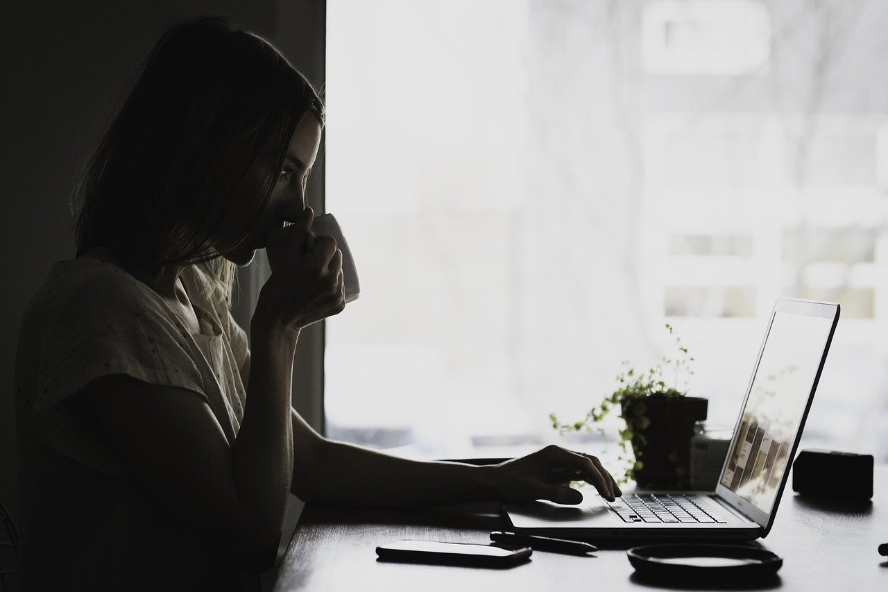 A woman sips coffee and reads infertility blogs on her laptop