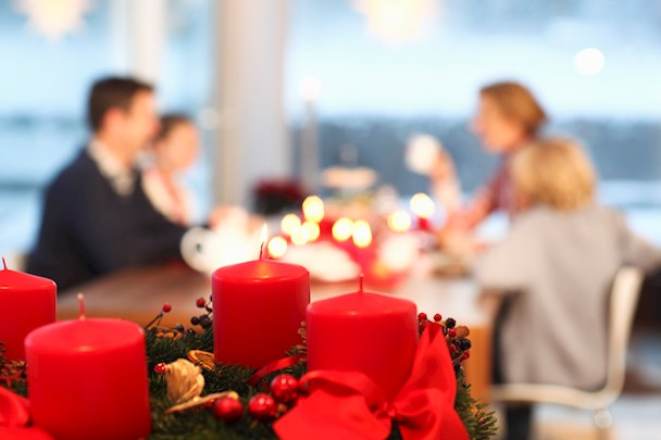 Blurry picture of a family at a dining table with red candles in the foreground