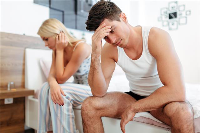 picture of couple in bedroom looking worried