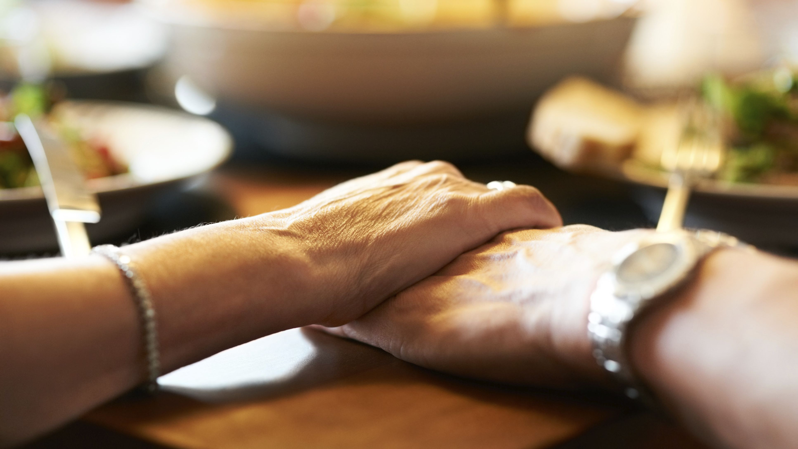 Picture of a person's hand holding another person's hand on top of a dining table
