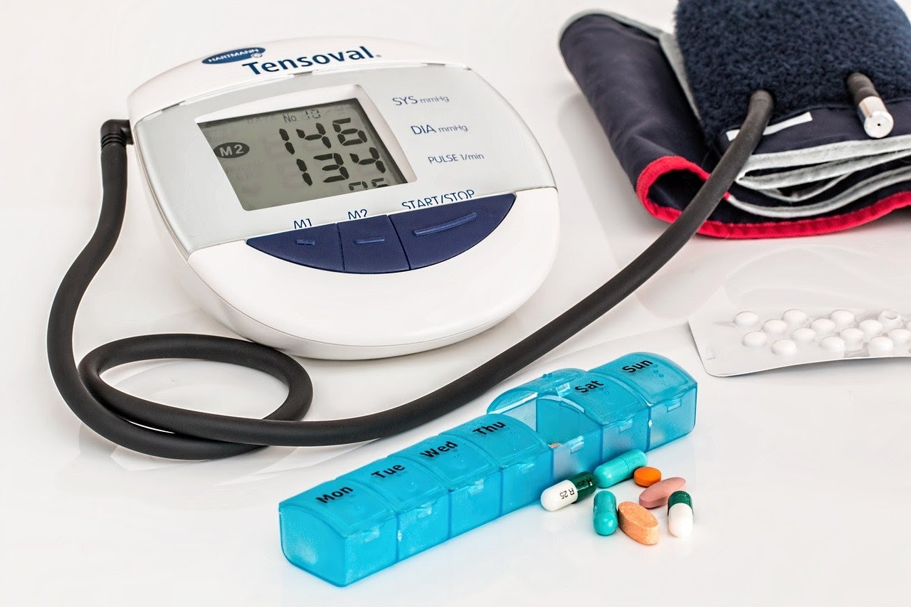 A layout of medical equipment, including a blood pressure measuring device and a case of pills