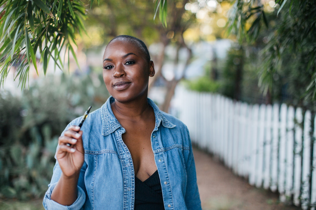 A black woman with a shaved head stands outside holding a vape pen.