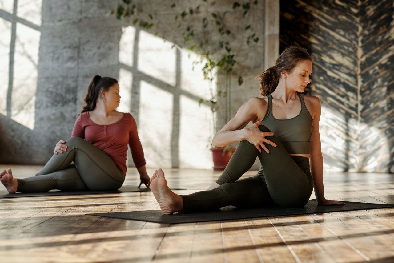 Two women sit stretching in an indoor yoga studio.