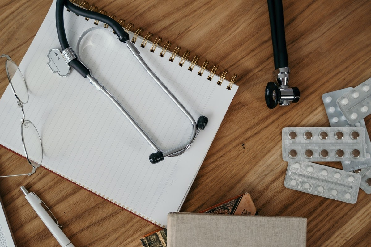 An image of doctors' tools, including glasses, a notebook, and a stethoscope