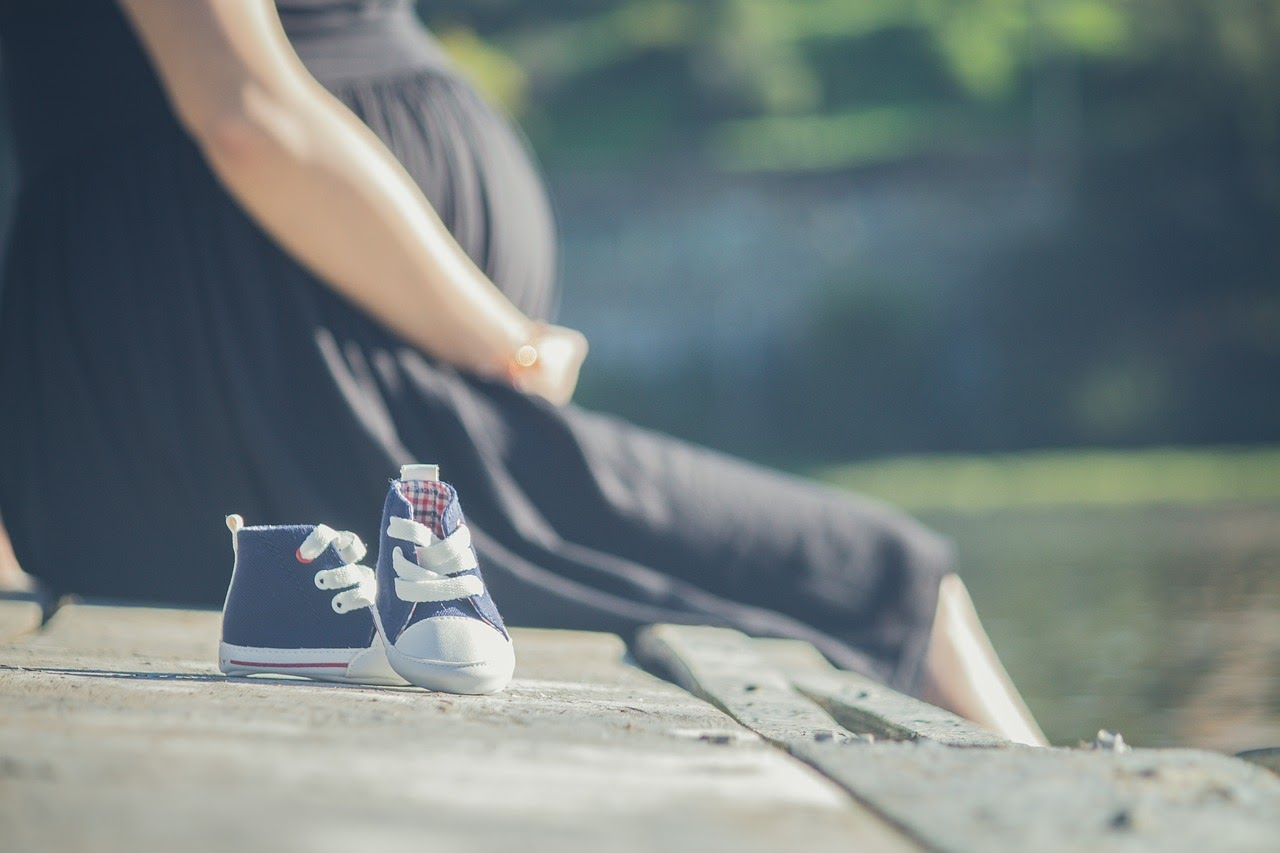 A pregnant woman sitting next to a pair of sneakers for a baby