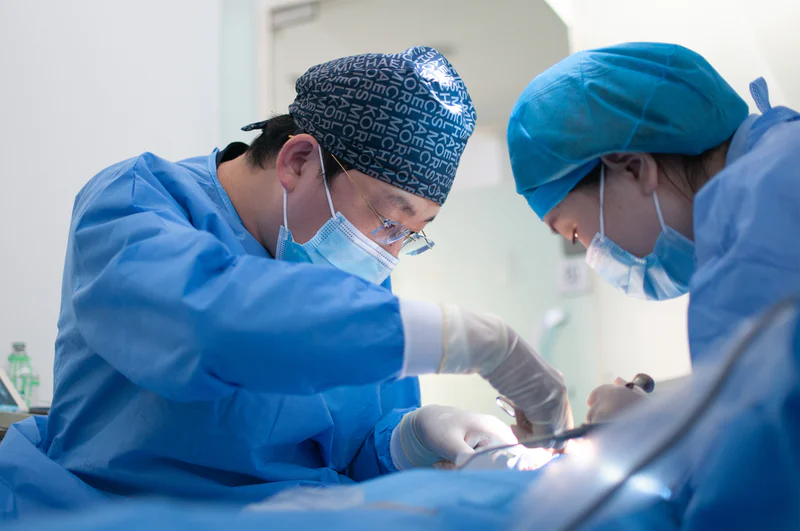 An image of two masked and gloved doctors performing a surgical procedure.