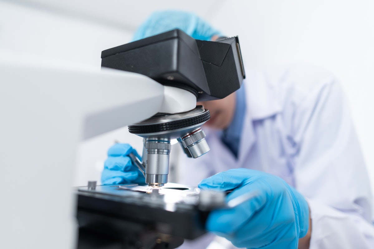 A doctor looks at a sample with a microscope.