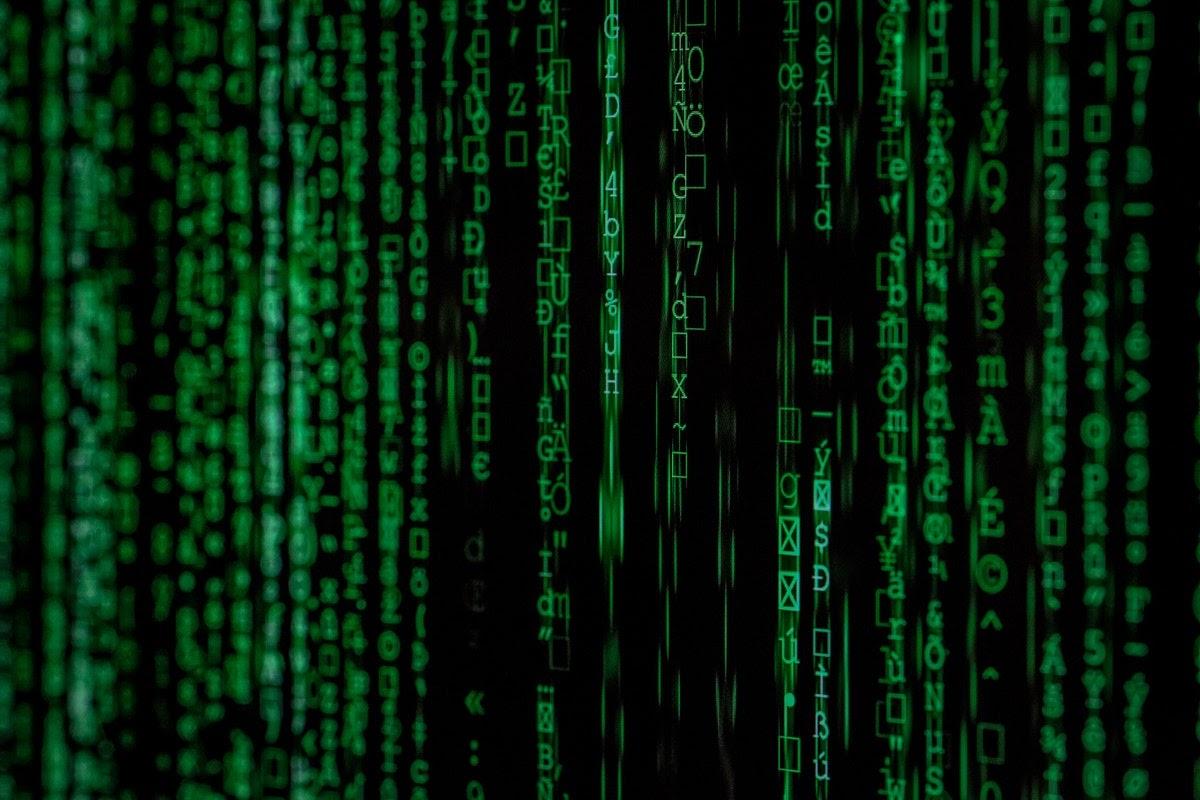 Green code symbols on a three-dimensional black screen