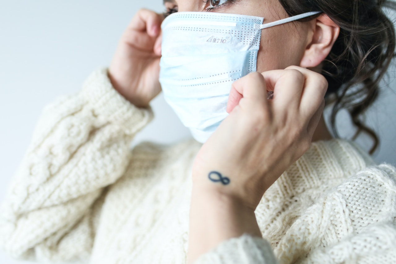 A woman in a cable knit sweater putting a surgical mask over her mouth and nose.