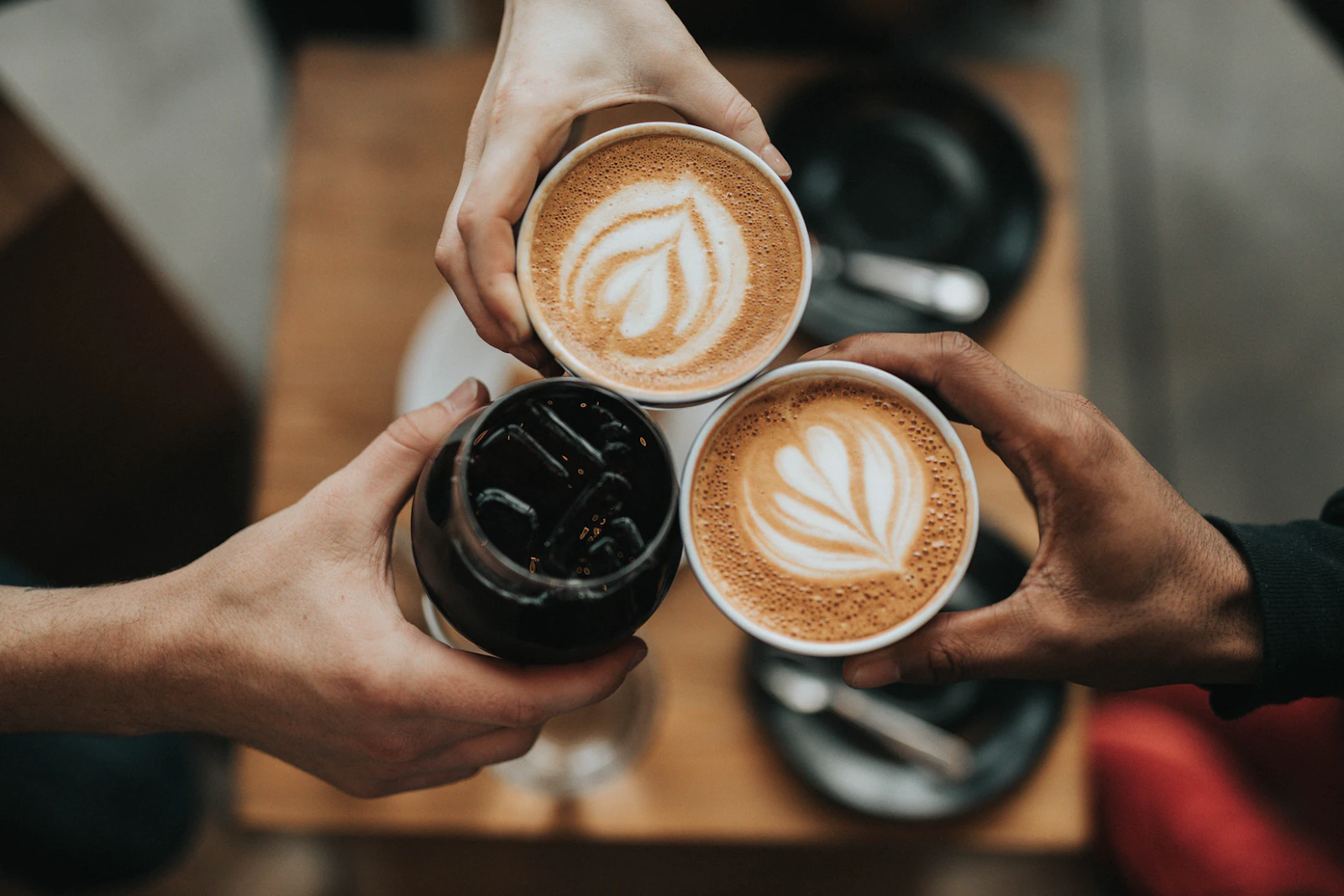 An image of three hands clinking three cups of coffee together in cheers, two hot with latte art and one iced.