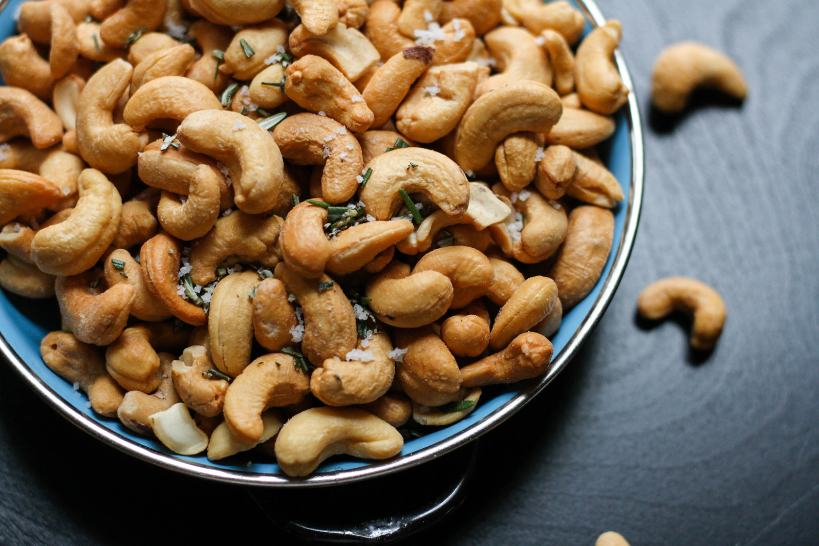 An image of a bowl of cashews sitting atop a dark, wooden table.