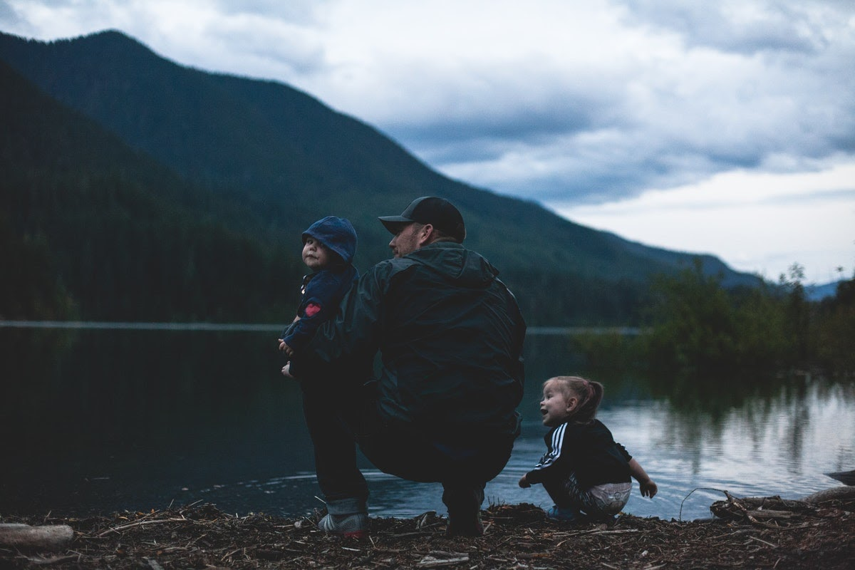 a father and two kids at the shore of a lake