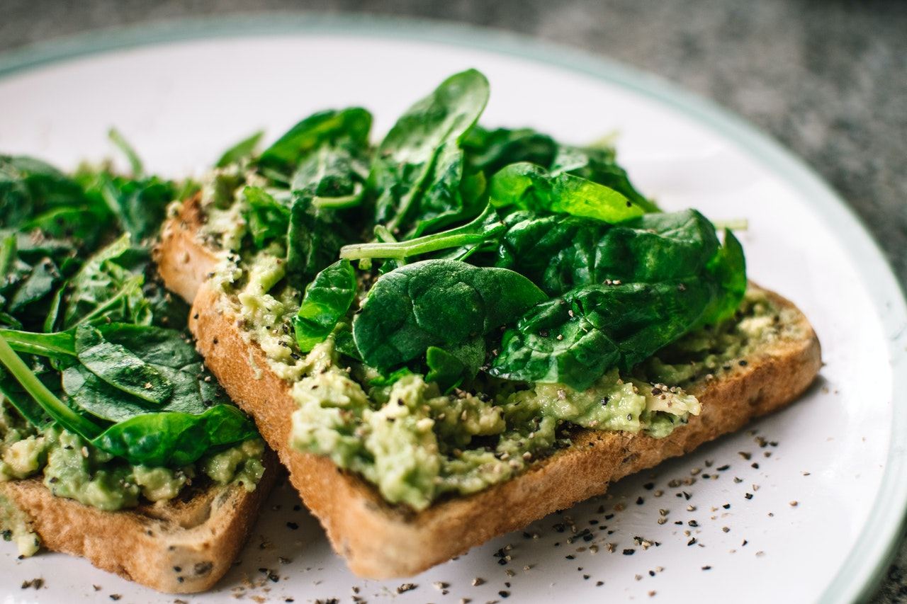 A closeup of toast with an avocado spread, spinach leaves, and seeds on top.