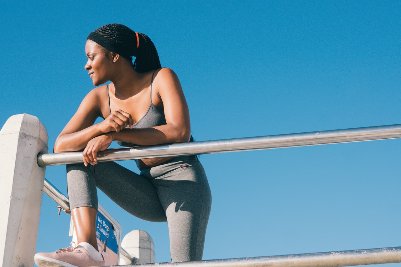 A black woman in grey exercise clothing stands outside with one leg balanced on a railing.