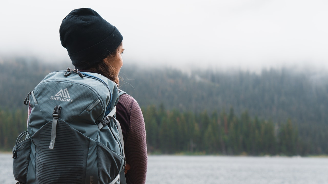 A woman with her back facing the viewer stands outdoors near a pine forest. She is wearing a light blue backpack, a purple shirt, and a black beanie.y