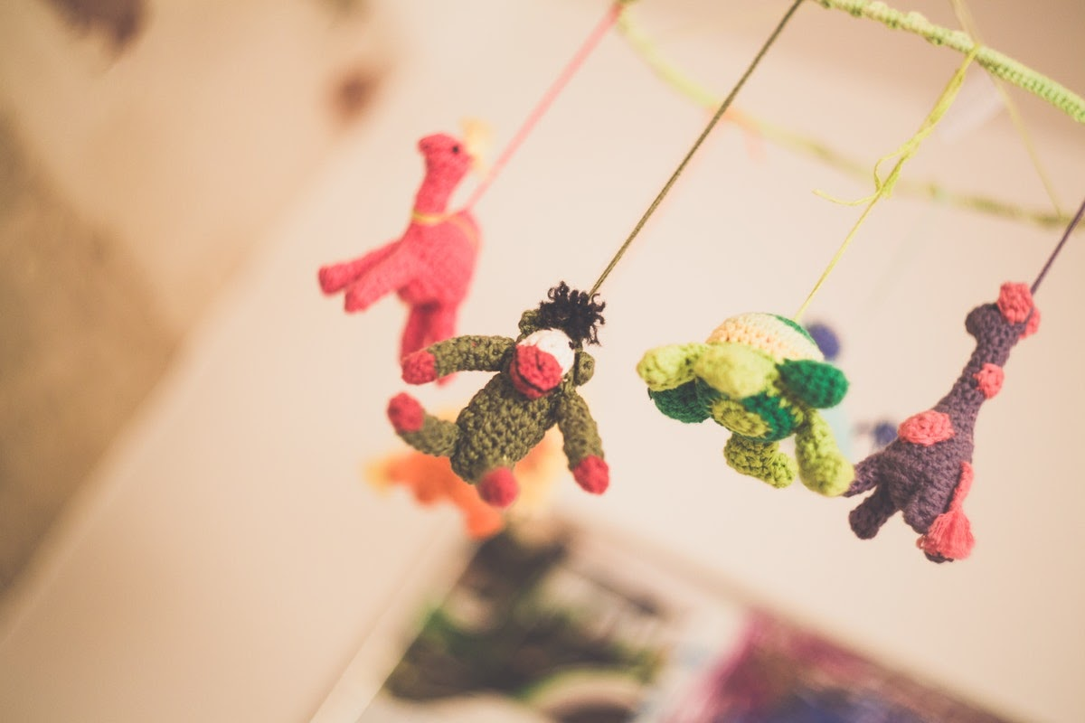 a baby mobile with hanging stuffed animals