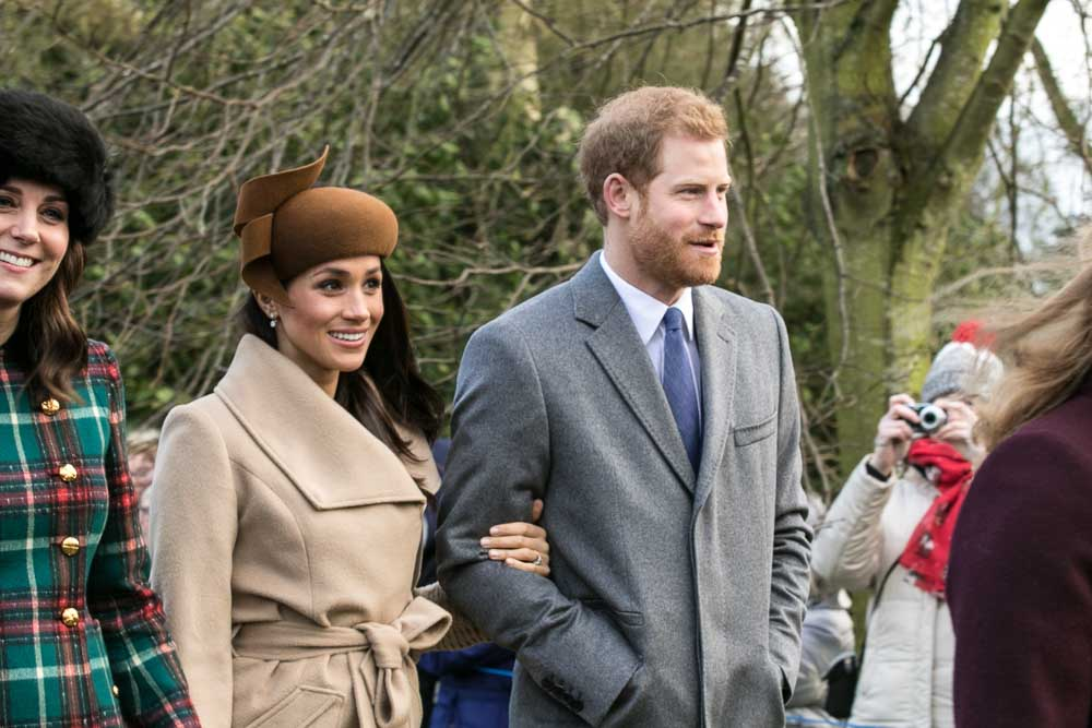 Meghan Markle and Prince Harry are shown from the waist up walking arm in arm on Christmas day 2017. Markle wears a beige overcoat with a brown hat while Harry wears a grey overcoat, white dress shirt, and blue tie. Kate Middleton stands to Markle's left.