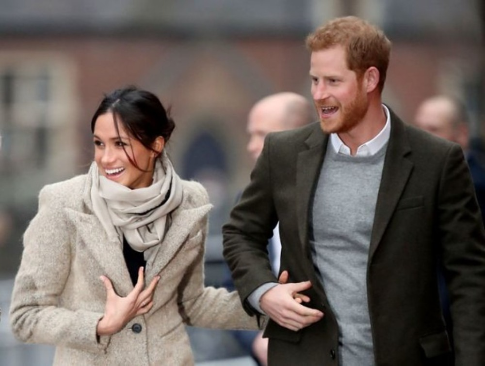 Meghan Markle and Prince Harry are shown from the waist up while holding hands and walking down the street.  They are both smiling and looking away from the camera in a candid shot.