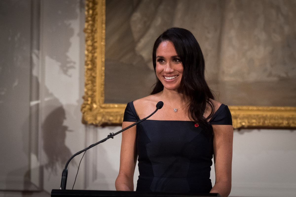 Meghan Markle stands alone at a podium with a microphone. She is wearing a navy blue gown and has her hair down. She smiles at an unseen crowd.