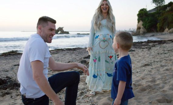 An image of Freddie, Chelsea, and their oldest son on the beach. Both parents are laughing as Charlie looks at his mother, who is visibly pregnant.
