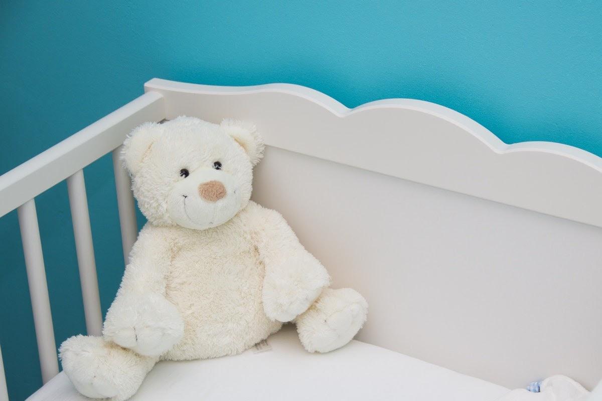 a stuffed teddy bear sitting in the corner of a white crib