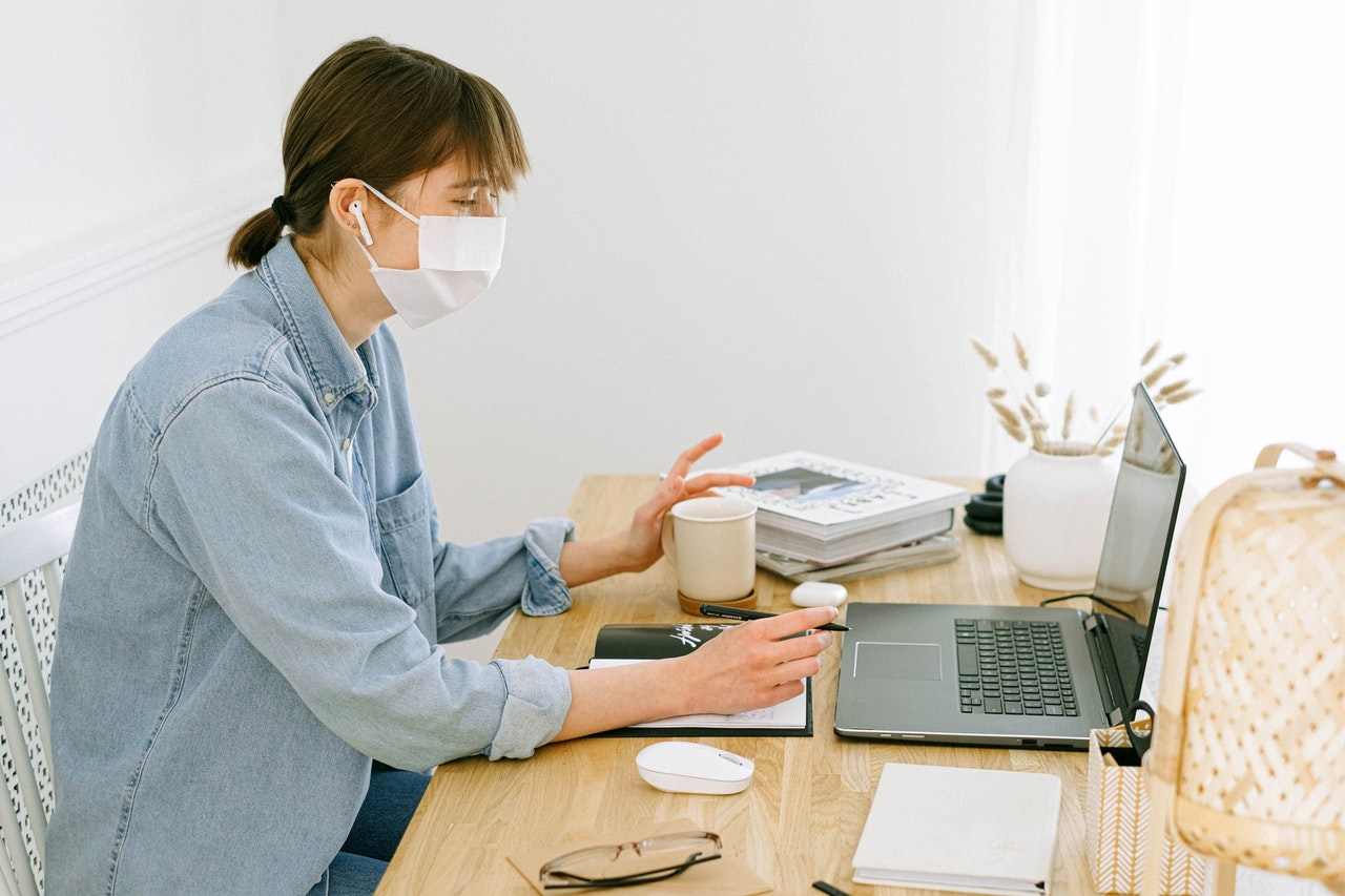 A woman in a denim button up shirt sits at a desk. She is wearing headphones and a medical mask. She appears to be having a conversation with a person on her computer.