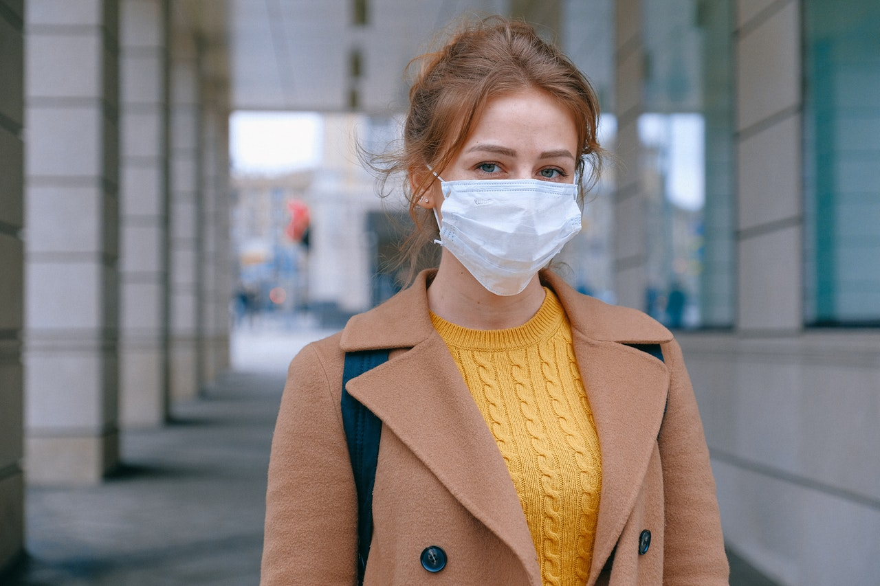 A woman stands outdoors. She has on a yellow cable knit sweater, a brown wool overcoat, a backpack, and a medical face mask.