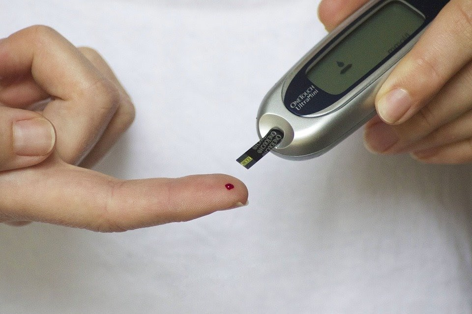 An image of someone pricking their finger with a small, handheld device. There is a small dot of blood on their finger.