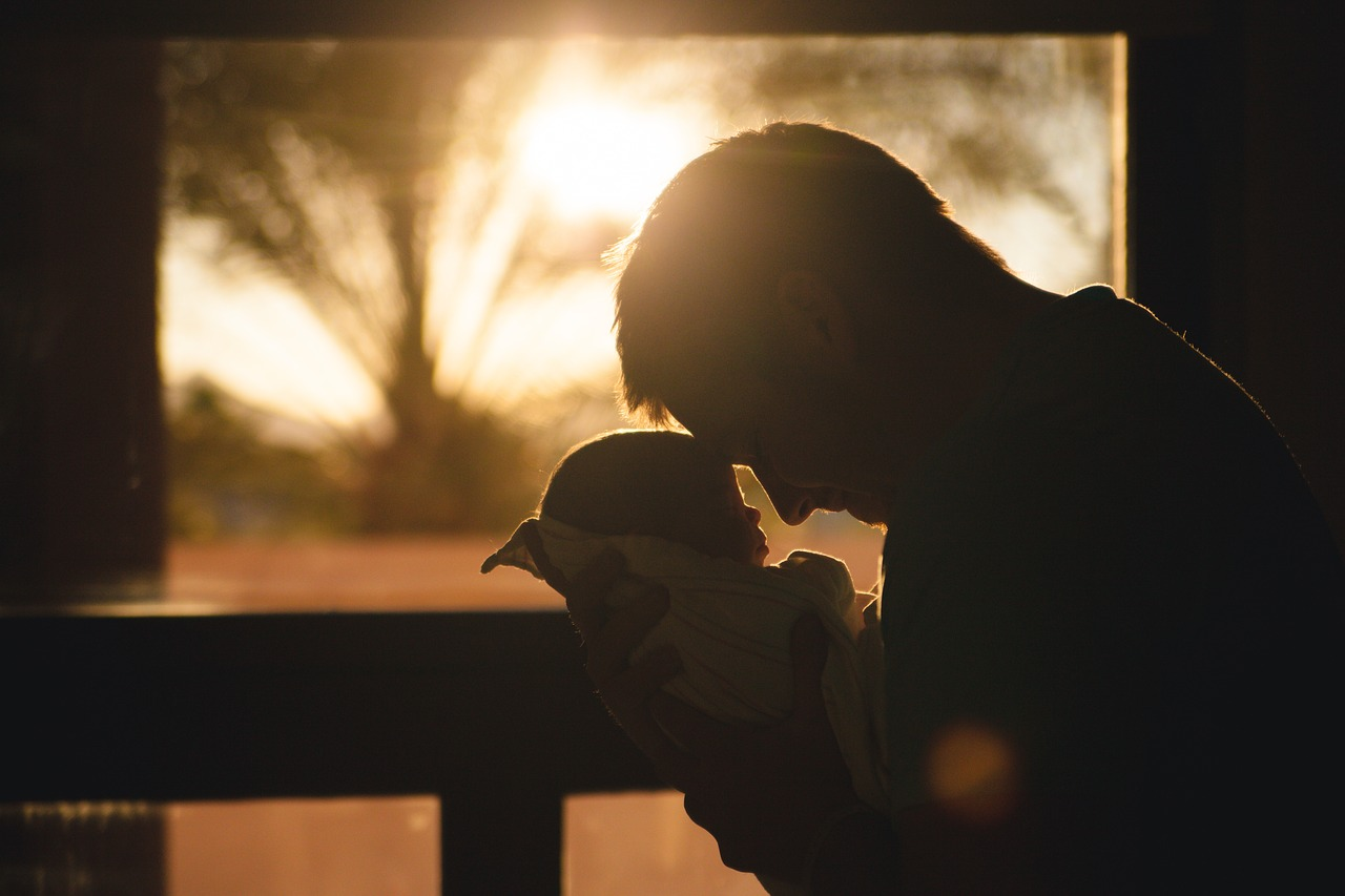An image of a man holding a baby wrapped in a blanket in front of a window. The sun is low in the sky, and the two have their foreheads pressed together.