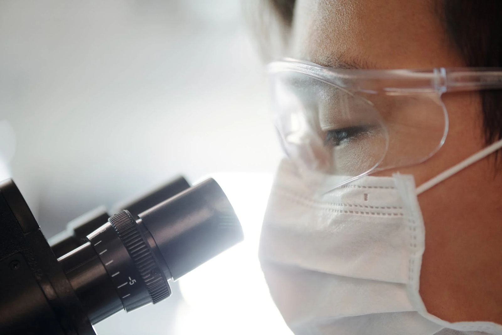 A close-up image of a researcher wearing both safety goggles and a mask looking into a microscope.