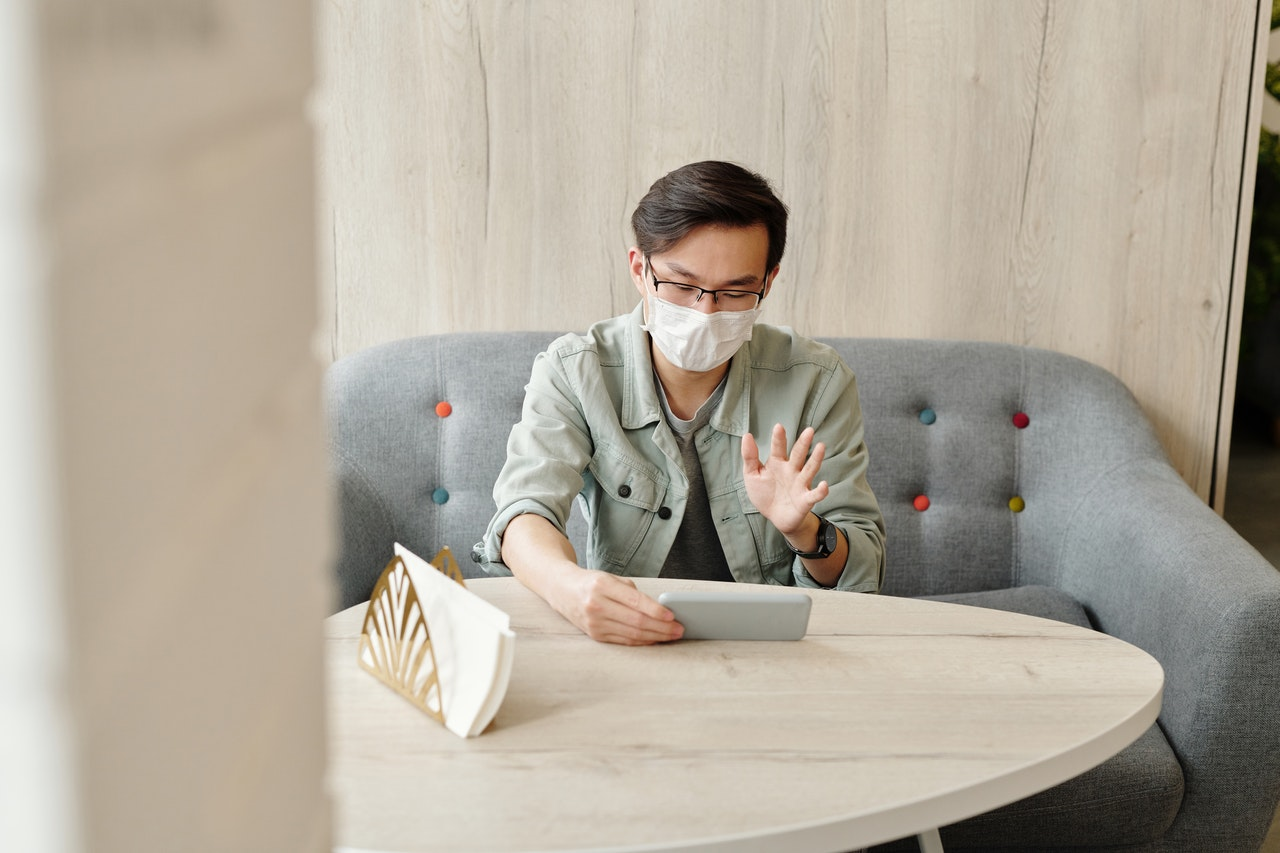 An Asian man with glasses sits on a grey couch. He is speaking to someone via Facetime on his phone and gesturing. He wears a medical face mask.