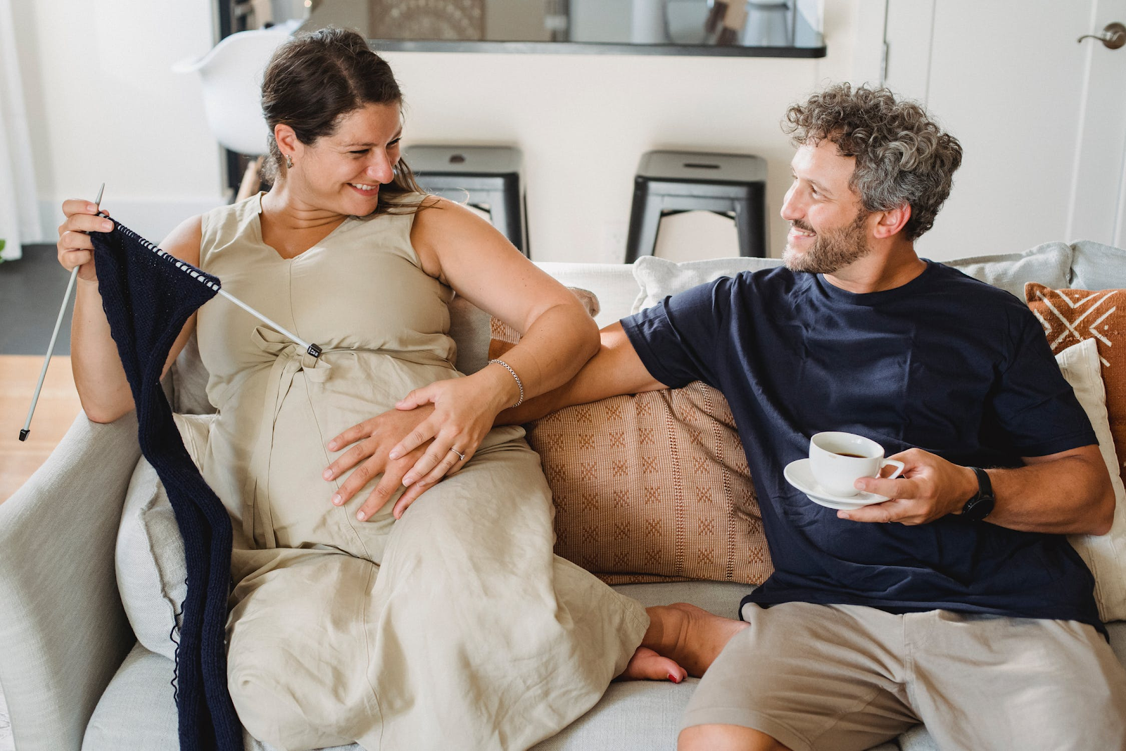 An image of a couple sitting on the couch. The woman on the left is pregnant and smiling, and holding one of the man's hands to her stomach. In his other hand, he's holding a cup of coffee.