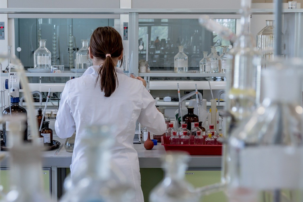 A woman stands in a science lab with her back to the viewer. She wears a white lab coat and has her hair pulled back into a ponytail. She is surrounded by beakers, vials, bottles, and other instruments.