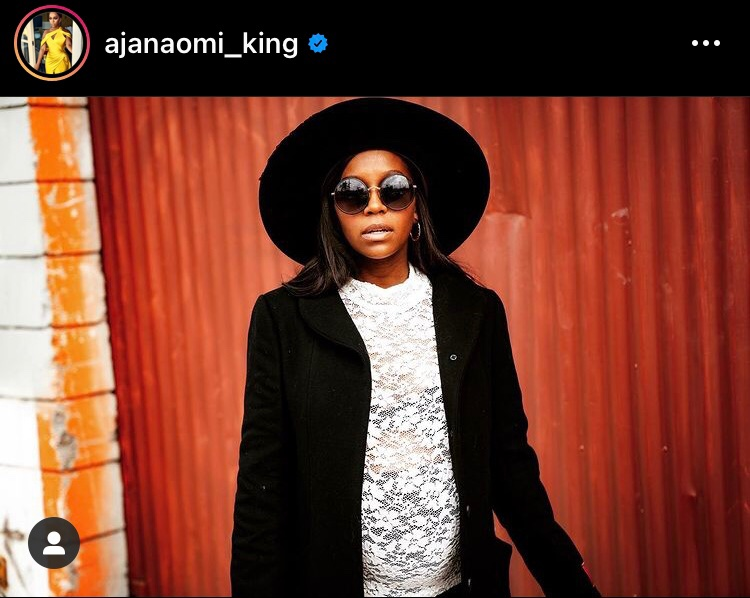 A screenshot of an instagram post by Aja Naomi King under the username @ajanaomi_king. King stands in the center of the frame wearing a wide brim hat, black circular sun glasses, a black coat, and a white, sheer, lace top. She is visibly pregnant.