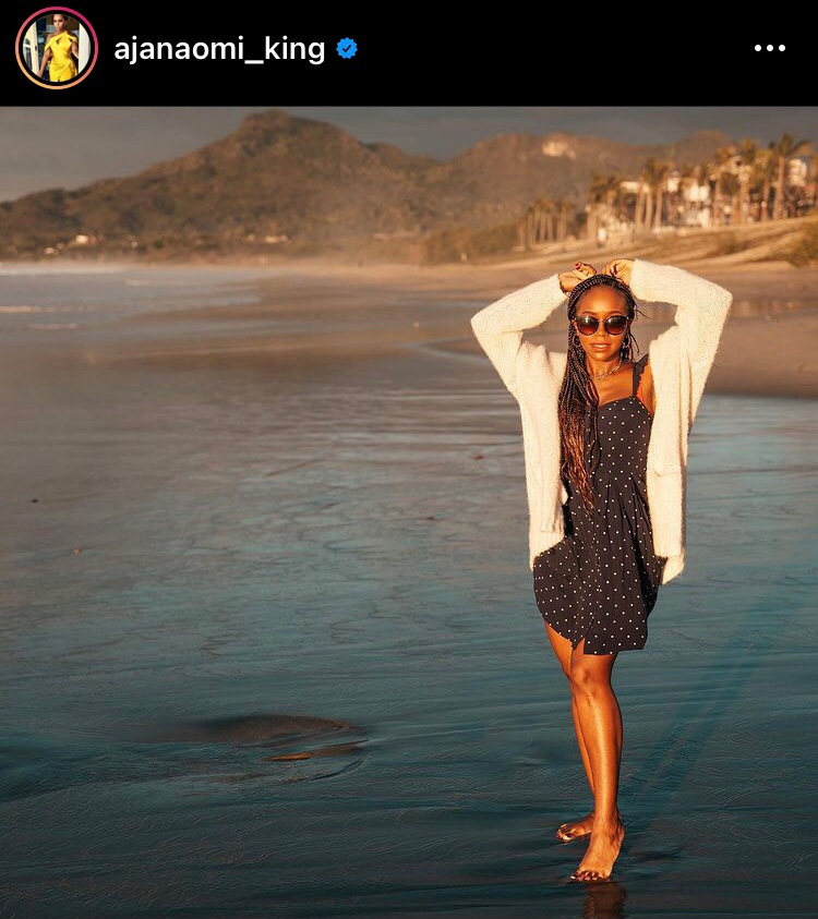 A screenshot of an instagram post by Aja Naomi King under the username @ajanaomi_king. King stands on a beach with her feet in the water. Her arms are raised above her head in a pose. She wears large sunglasses, a white cardigan, and a black and white polka dot dress. Her hair is in long braids.