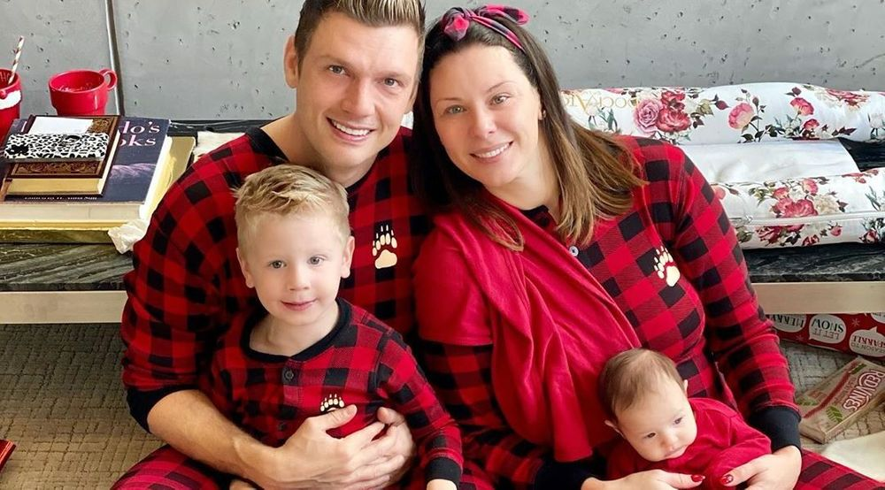 An image of the four Carters all sitting on their carpet in matching red plaid pajamas with a paw print on the front. Nick is holding their son Odin and Lauren is holding their daughter Saoirse.